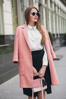 Привлекательная стильная улыбающаяся богатая женщина гуляет по городской улице в розовом пальто весенней модной тенденции, держа кошелек, элегантный стиль, в солнцезащитных очках