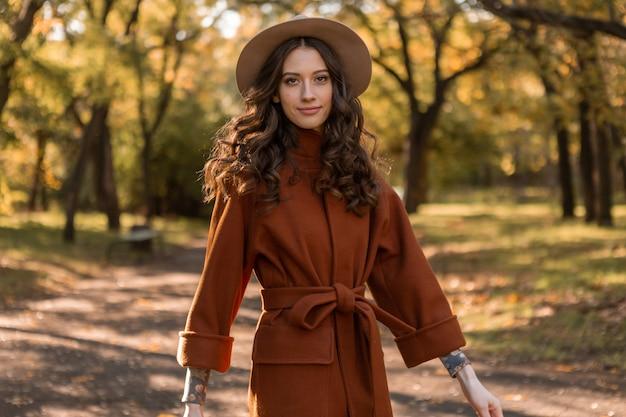 Привлекательная стильная улыбающаяся тощая женщина с вьющимися волосами гуляет в парке, одетая в теплое коричневое пальто, осенний модный уличный стиль