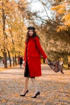 暖かい赤いコートの秋の流行のファッション、ストリートスタイル、ベレー帽の帽子とヒョウ柄のスカーフを身に着けて公園を歩く巻き毛の魅力的なスタイリッシュな笑顔の細い女性