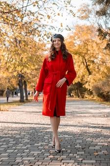 따뜻한 빨간 코트 가을 유행 패션, 거리 스타일을 입고 공원에서 산책하는 곱슬 머리를 가진 매력적인 세련된 웃는 마른 여자, 베레모 모자를 쓰고