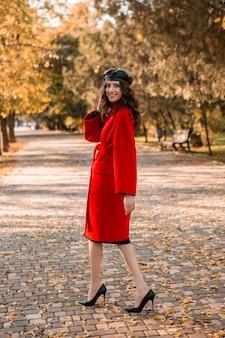 暖かい赤いコート秋の流行のファッション、ストリートスタイル、ベレー帽の帽子をかぶって公園を歩いている巻き毛の魅力的なスタイリッシュな笑顔の細い女性