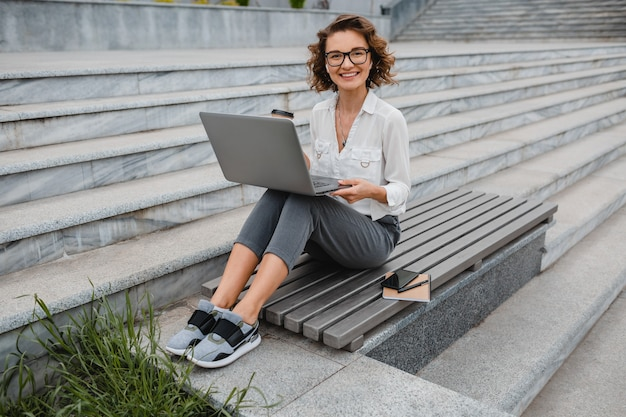 Attractive stylish smiling woman in glasses working typing on laptop