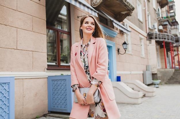 イヤホンで音楽を聴くピンクのコートで街を歩いて魅力的なスタイリッシュな笑顔の女性