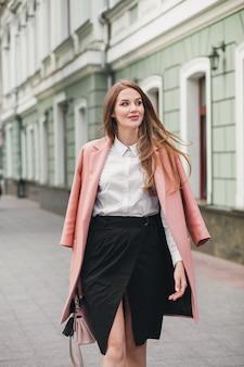 Привлекательная стильная улыбающаяся женщина гуляет по городской улице в розовом пальто весенней модной тенденции, элегантном стиле