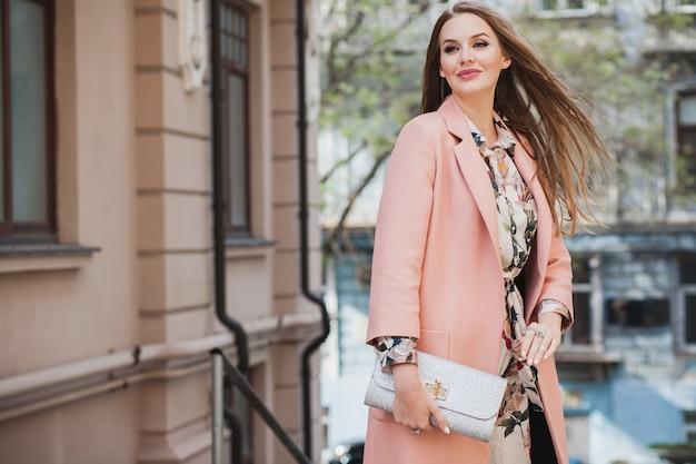 Привлекательная стильная улыбающаяся женщина гуляет по городской улице в розовом пальто весенней модной тенденции, держащей кошелек