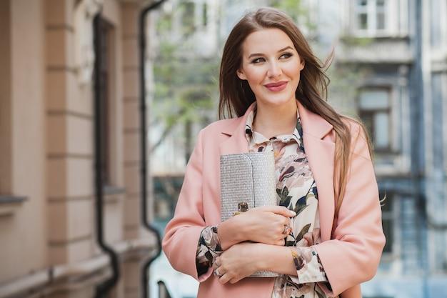 魅力的なスタイリッシュな笑顔の女性がピンクのコート春のファッショントレンドの財布を持って街を歩く