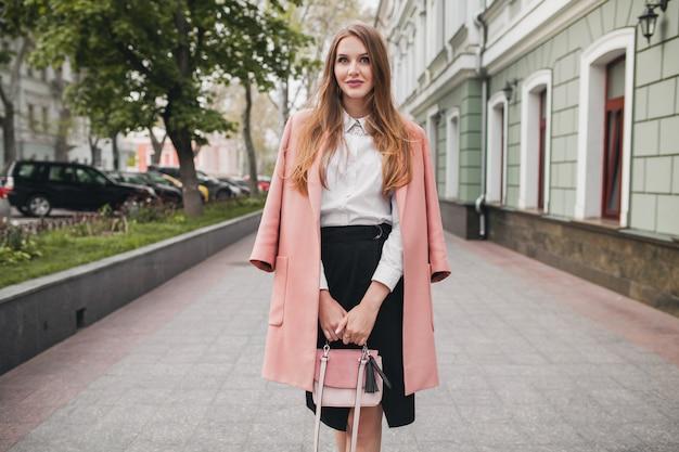 Привлекательная стильная улыбающаяся женщина гуляет по городской улице в розовом пальто
