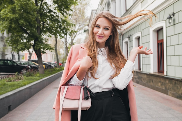 Attractive stylish smiling woman walking city street in pink coat