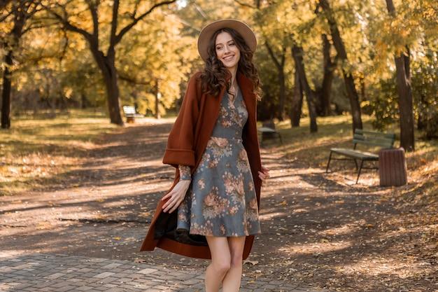 プリントドレスと暖かいコートを着て公園を歩く巻き毛の魅力的なスタイリッシュな笑顔の女性秋の流行のファッション、ストリートスタイル