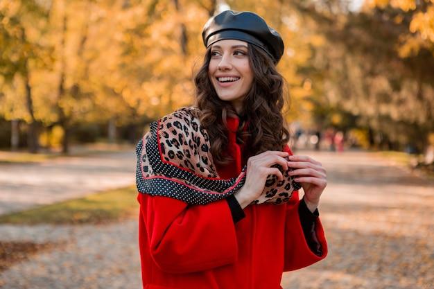暖かい赤いコートの秋の流行のファッション、ストリートスタイル、ベレー帽の帽子とヒョウ柄のスカーフを身に着けて公園を歩く巻き毛の魅力的なスタイリッシュな笑顔の女性