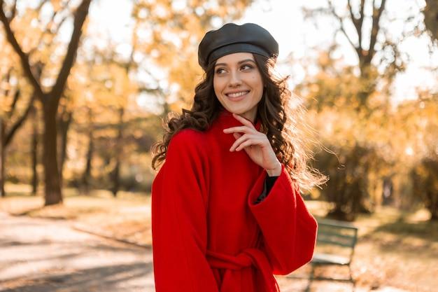 따뜻한 빨간 코트 가을 유행 패션, 거리 스타일을 입고 공원에서 산책하는 곱슬 머리를 가진 매력적인 세련된 웃는 여자, 베레모 모자를 쓰고