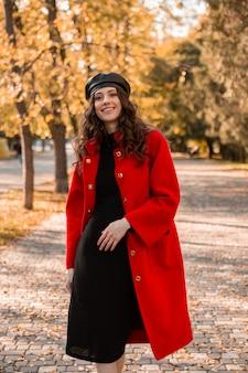 暖かい赤いコート秋の流行のファッション、ストリートスタイル、ベレー帽の帽子をかぶって公園を歩く巻き毛の魅力的なスタイリッシュな笑顔の女性