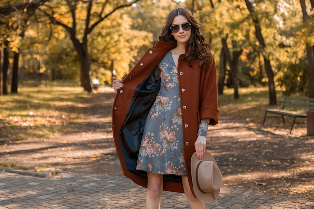Attractive stylish smiling woman with curly hair walking in park dressed in warm brown coat autumn trendy fashion, street style wearing hat and sunglasses