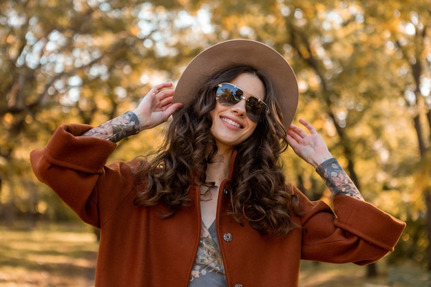 Attractive stylish smiling woman with curly hair walking in street park dressed in warm brown coat autumn trendy fashion, street style wearing hat and sunglasses