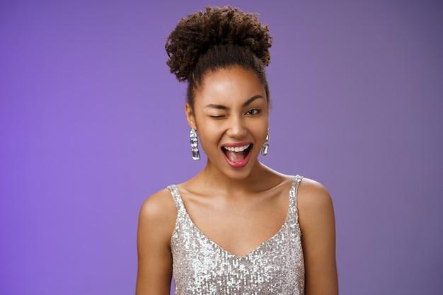魅力的なスタイリッシュで裕福なアフリカ系アメリカ人の女性が豪華なイヤリングのシルバーのドレスをまばたきして、すべてが大丈夫であることを保証します。
