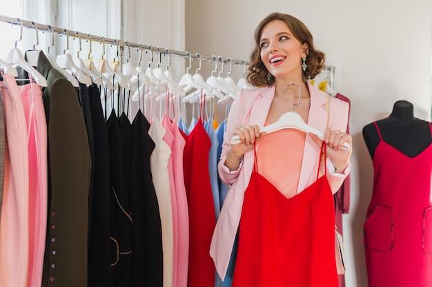 Привлекательная стильная женщина, выбирающая одежду в магазине одежды