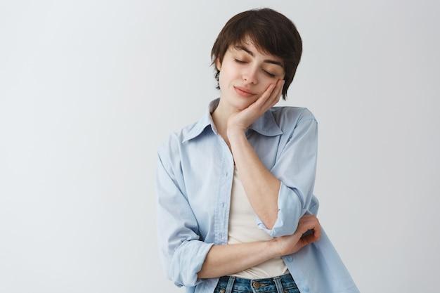 Attraente donna alla moda chiudere gli occhi e appoggiandosi al palmo per fare un pisolino, dormire