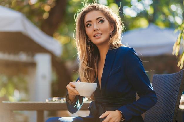 カプチーノのカップを飲むカフェのテーブルに座っている青いエレガントなスーツに身を包んだ魅力的なスタイリッシュな女性