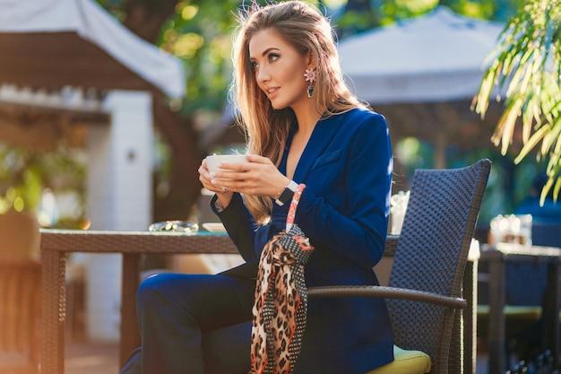 Привлекательная стильная женщина, одетая в синий элегантный костюм, сидит за столом в кафе, пьет чашку капучино