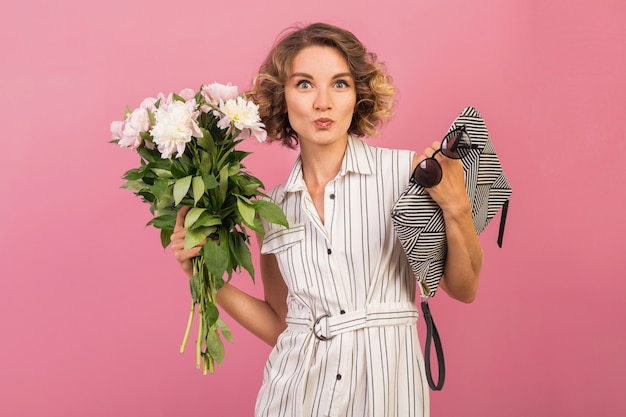 Attractive stylish woman in elegant white striped dress holding handbag and bouquet