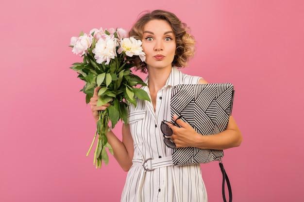 Привлекательная стильная женщина в элегантном белом полосатом платье держит сумочку и букет
