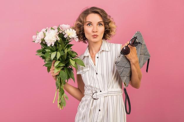 ハンドバッグと花束を保持しているエレガントな白い縞模様のドレスで魅力的なスタイリッシュな女性