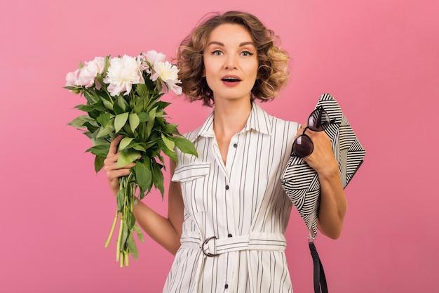 ピンクのスタジオの背景の感情的な表情、エレガントな白い縞模様のドレスで魅力的なスタイリッシュな女性驚いた、ハンドバッグ、花束、面白い、巻き毛のヘアスタイル、ファッション夏トレンドアクセサリー