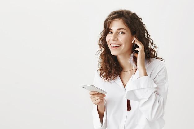 Привлекательная стильная женщина слушает музыку в беспроводных наушниках, держа смартфон