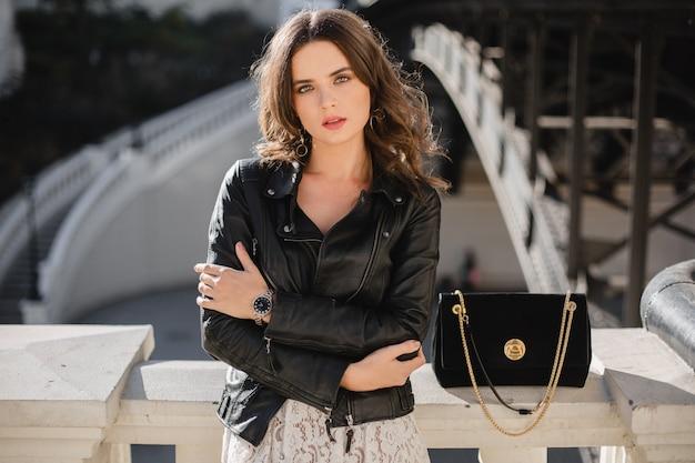 ファッショナブルな服装、スエードのハンドバッグ、黒い革のジャケットと白いレースのドレスを着て、春秋スタイルでストリートでポーズをとる魅力的なスタイリッシュな女性