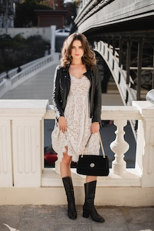 Attractive stylish woman posing in street in fashionable outfit, suede handbag, wearing black leather jacket and white lace dress, high boots, spring autumn style