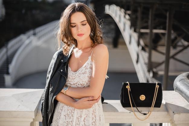 Attraente donna elegante in posa in strada in abito alla moda, borsa in pelle scamosciata, indossa giacca di pelle nera e abito di pizzo bianco, stile primavera autunno