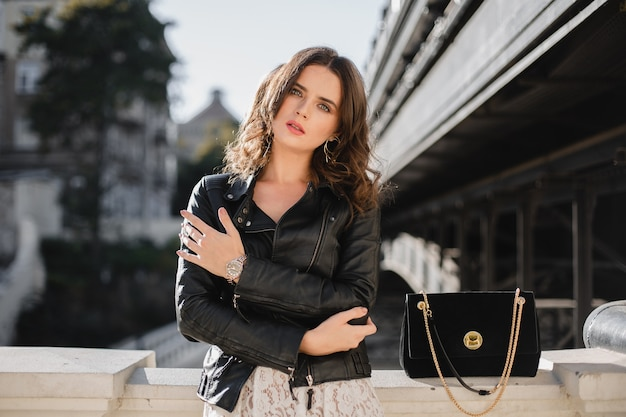 Attractive stylish woman posing in street in fashionable outfit, suede handbag, wearing black leather jacket and white lace dress, spring autumn style