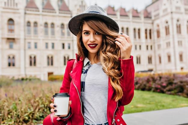 Attraente donna alla moda in posa con un sorriso dolce e tenendo la tazza di caffè al mattino