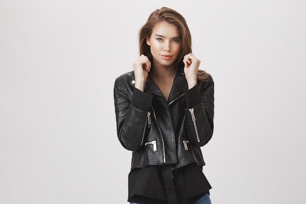 魅力的なスタイリッシュな女性のプルカラージャケットと生意気な笑顔
