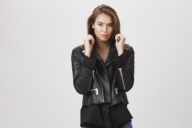 Attractive stylish woman pull collar jacket and smile sassy