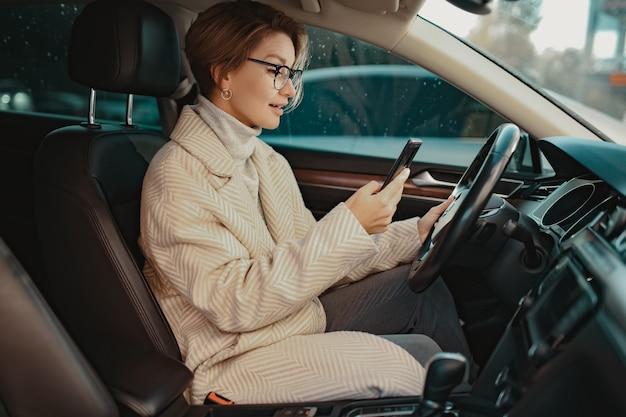 Привлекательная стильная женщина, сидящая в машине, одетая в зимнее пальто и очки, с помощью смартфона