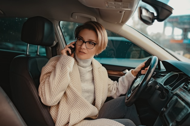 スマートフォンを使用してコートの冬のスタイルとメガネに身を包んだ車に座っている魅力的なスタイリッシュな女性