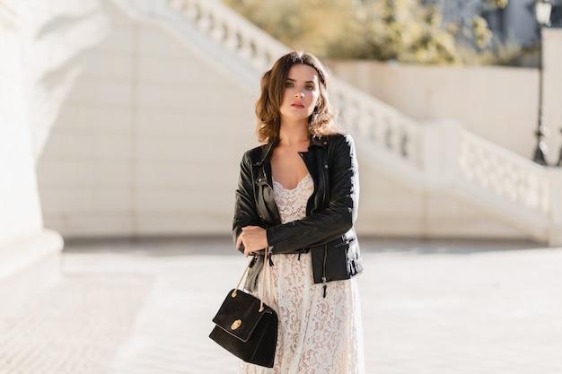 ファッショナブルな服装で通りを歩いて、財布を持って、黒い革のジャケットと白いレースのドレスを着て、春秋スタイルの魅力的なスタイリッシュな女性