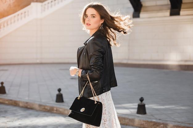 Привлекательная стильная женщина гуляет по улице в модном наряде, держит замшевую сумочку, в черной кожаной куртке и белом кружевном платье, весенне-осенний стиль, поворачиваясь в движении