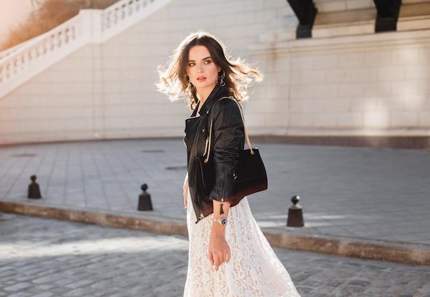 ファッショナブルな服装で通りを歩いている魅力的なスタイリッシュな女性、スエードのハンドバッグを持って、黒い革のジャケットと白いレースのドレスを着て、春秋スタイル、動きを振り返る