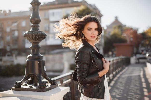 Привлекательная стильная женщина гуляет по улице в модном наряде, размахивая волосами на ветру, в черной кожаной куртке и белом кружевном платье в весенне-осеннем стиле