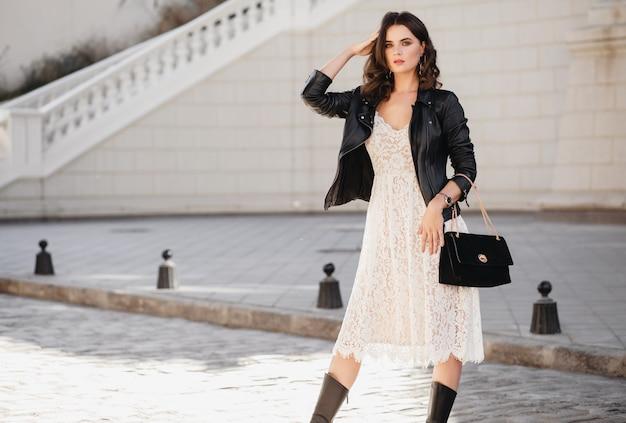 Attraente donna elegante che cammina per strada in abito alla moda, tenendo la borsa, indossa una giacca di pelle nera e abito di pizzo bianco, stile primavera autunno