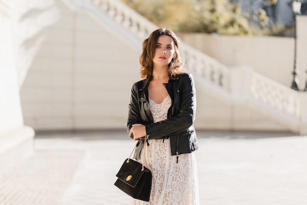 Attractive stylish woman walking in street in fashionable outfit, holding purse, wearing black leather jacket and white lace dress, spring autumn style