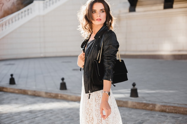 Attractive stylish woman walking in street in fashionable outfit, holding suede handbag, wearing black leather jacket and white lace dress, spring autumn style, turning around in motion
