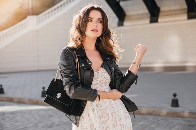 Attractive stylish woman walking in street in fashionable outfit, holding suede handbag, wearing black leather jacket and white lace dress, spring autumn style,