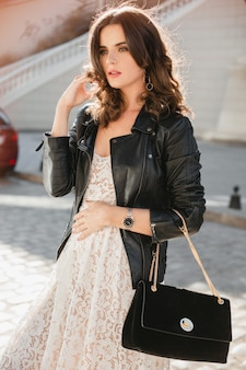 Attractive stylish woman walking in street in fashionable outfit, holding suede handbag, wearing black leather jacket and white lace dress, spring autumn style