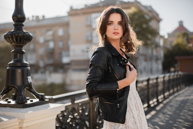 Attractive stylish woman walking in street in fashionable outfit holding suede handbag wearing black leather jacket and white lace dress, spring autumn style