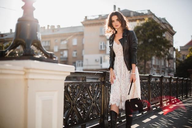Attraente donna elegante che cammina in strada in abito alla moda che tiene borsa in pelle scamosciata indossa giacca di pelle nera e abito di pizzo bianco, stile primavera autunno