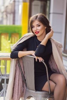 黒のドレスに身を包んだ黒髪を集めた魅力的なスタイリッシュな女性