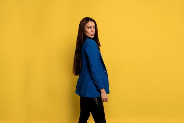 魅力的な笑顔で孤立した壁の上にポーズをとって青いジャケットを着て長い黒髪の魅力的なスタイリッシュな女性